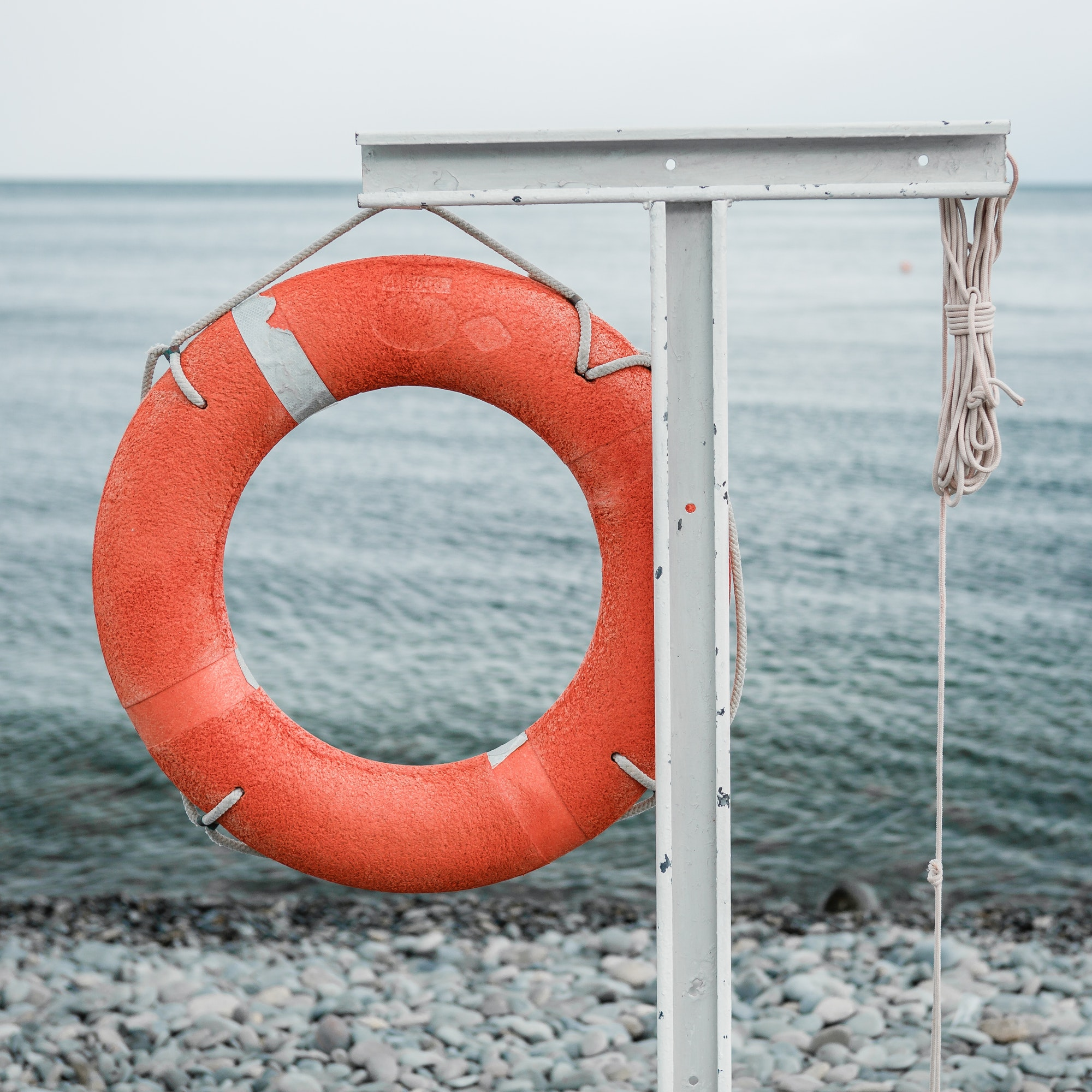 orange lifebuoy on the sea coast